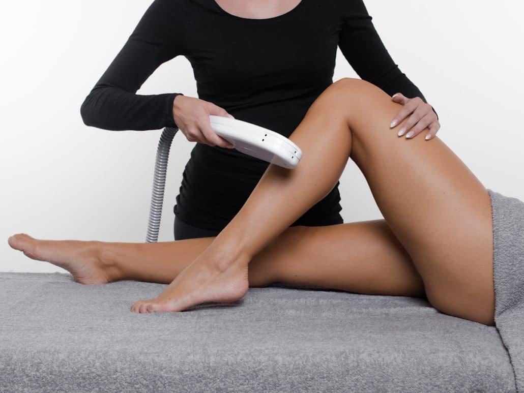Esthéticienne en train de faire une épilation définitive au laser sur les jambes d'une cliente